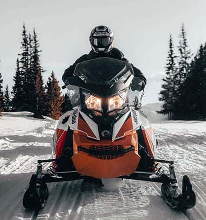 Snowmobile facing the camera ready to ride the trails